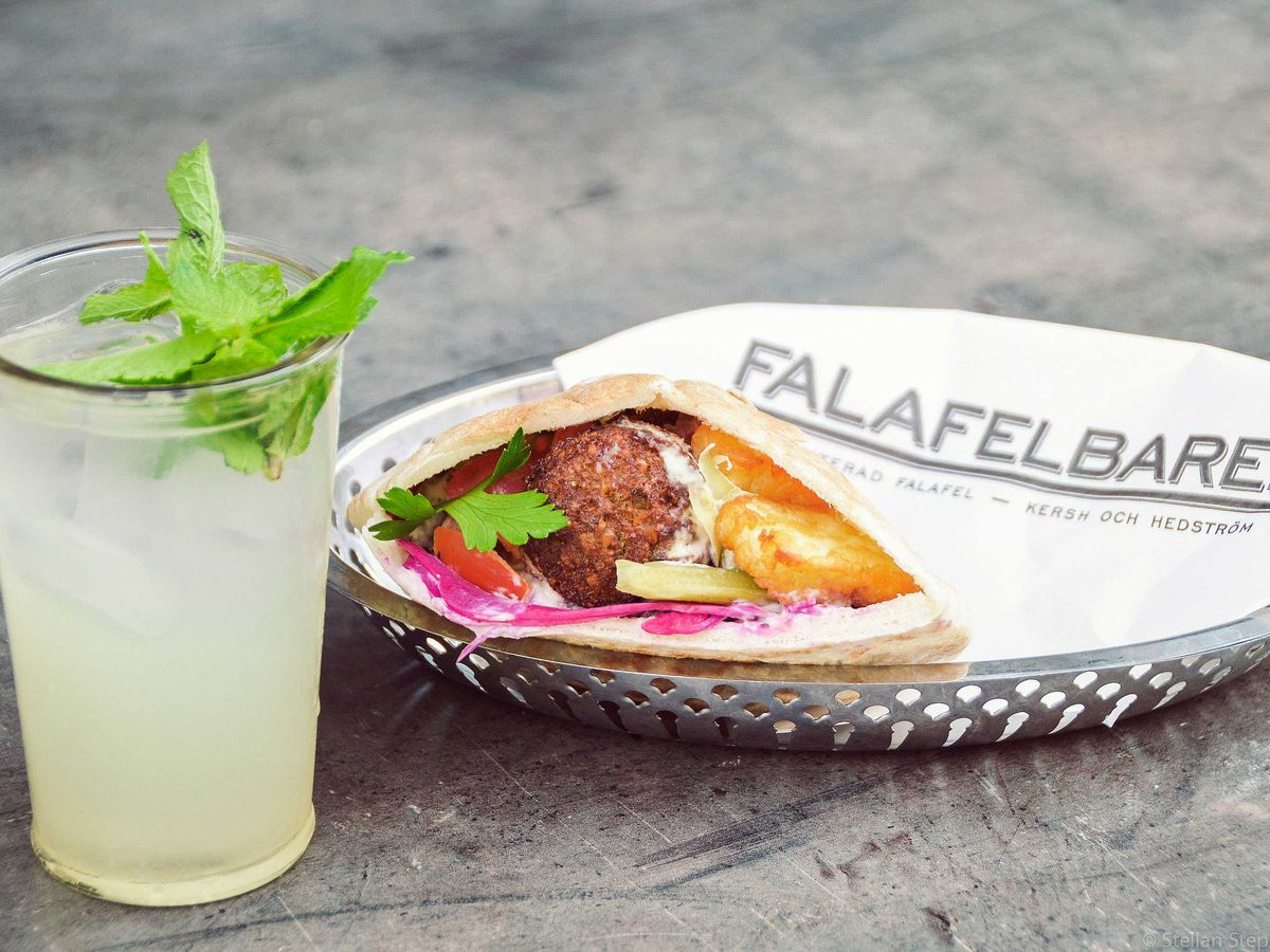 Falafel and fixings in a pita sandwich wrapped in branded wax paper on a plate beside a mint-garnished drink