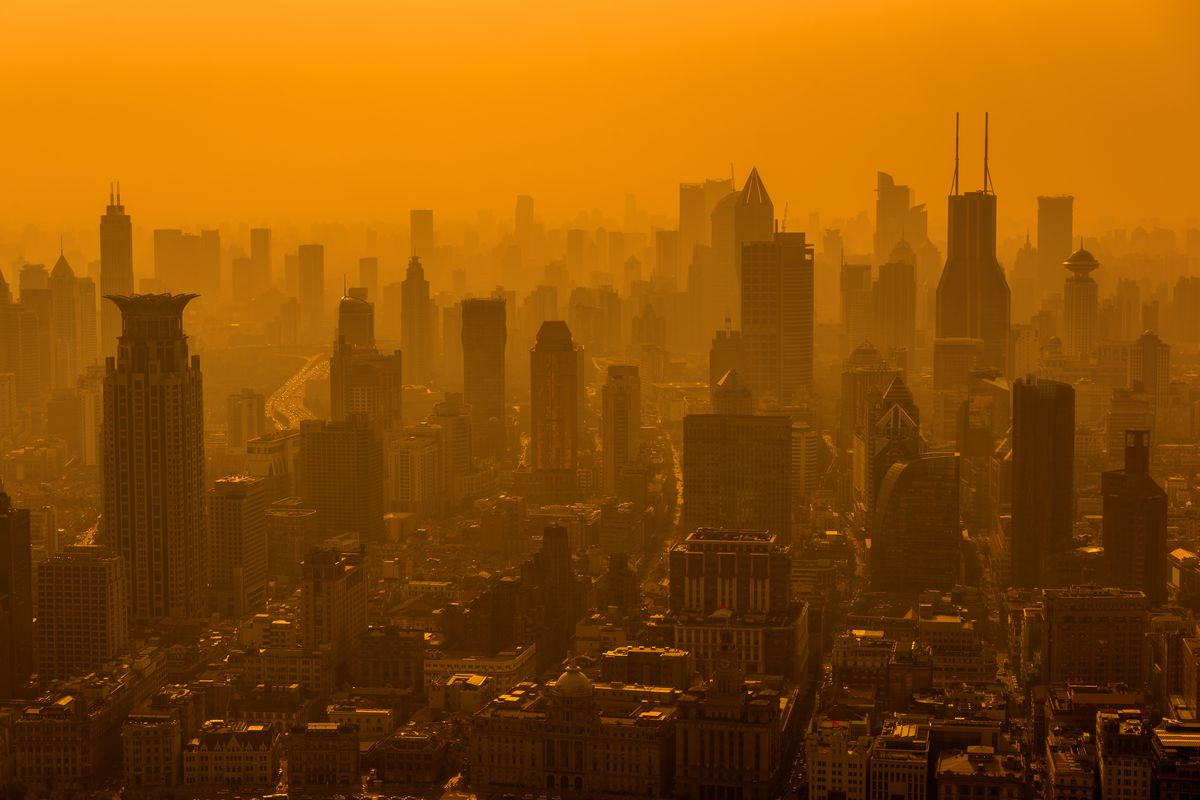 The skyline of a modern city seen through an orangish-brown sky, the result of high levels of air pollution.