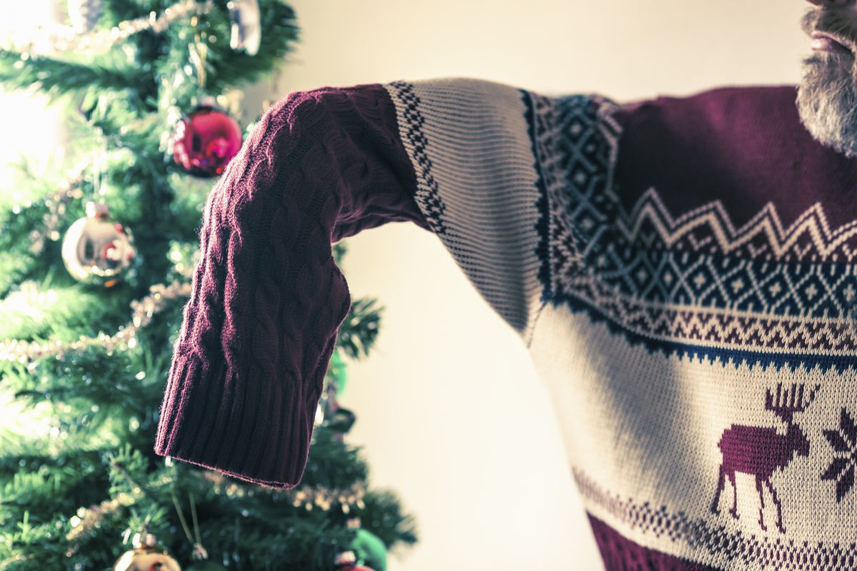 A person putting on a sweater in front of a Christmas tree.