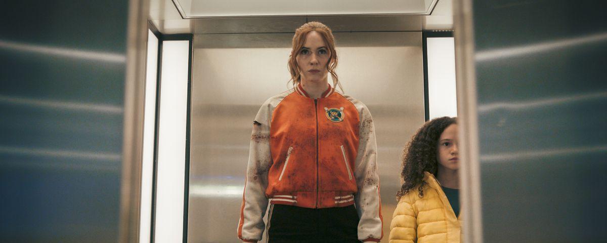 Karen Gillan as Sam and Chloe Coleman as Emily stand in an elevator in Gunpowder Milkshake