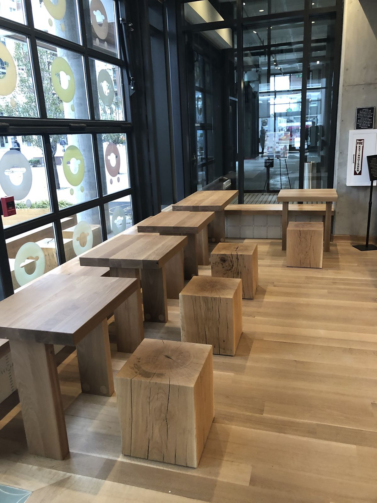A photo of wooden tables and cubes for seating facing a large window inside Kaffe Landskap at Union Station
