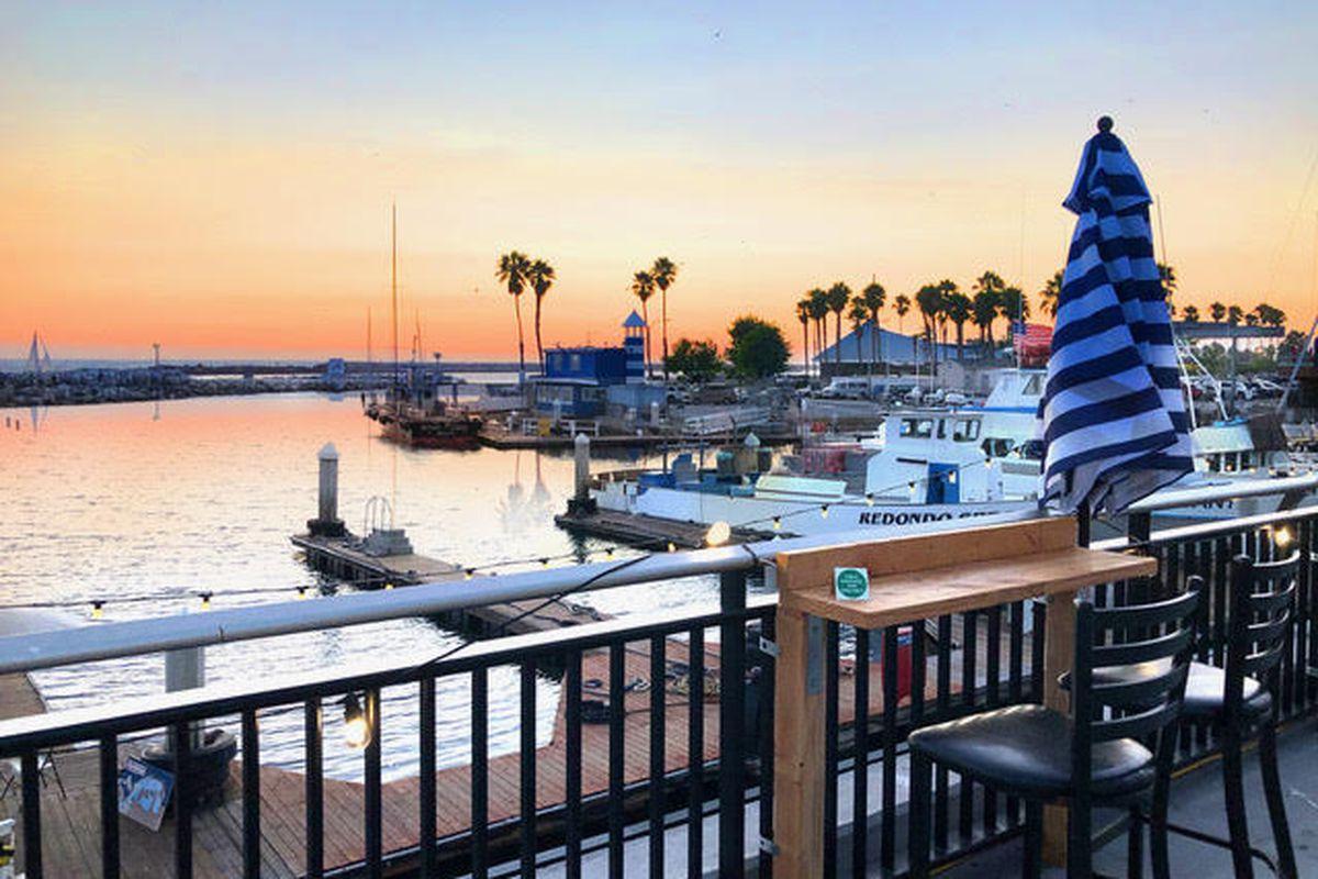 A new al fresco dining setup overlooks a marina at sunset.