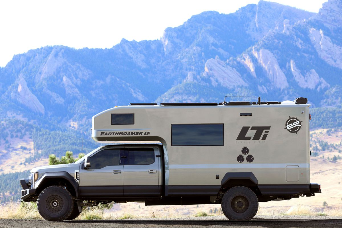 A side view of a silver camper. Black lettering says LTi on the side with the EarthRoamer logo, and there are mountains in the background.