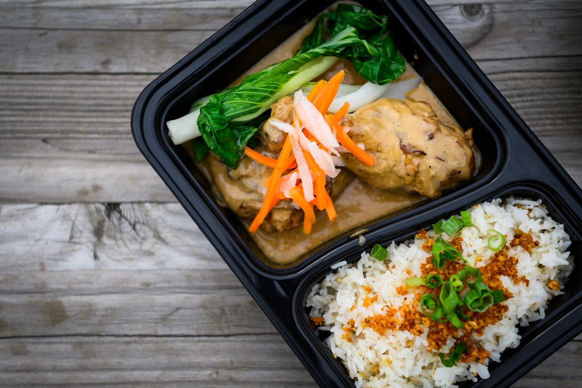 A takeout container from Baon Kainan in Portland Oregon, filled with two pieces of chicken in a light brown sauce, topped with pickled daikon and carrots and steamed bok choy.