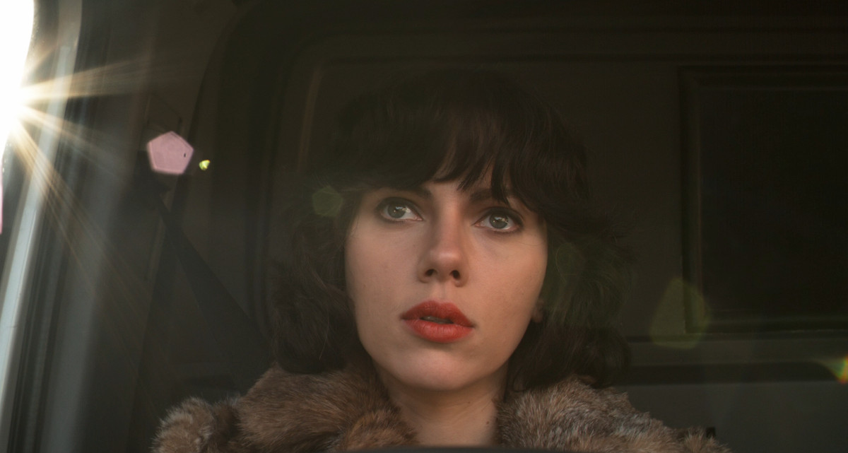 scarlett johansson as an alien with black hair and red lipstick sitting in a van as the sun flares through the window