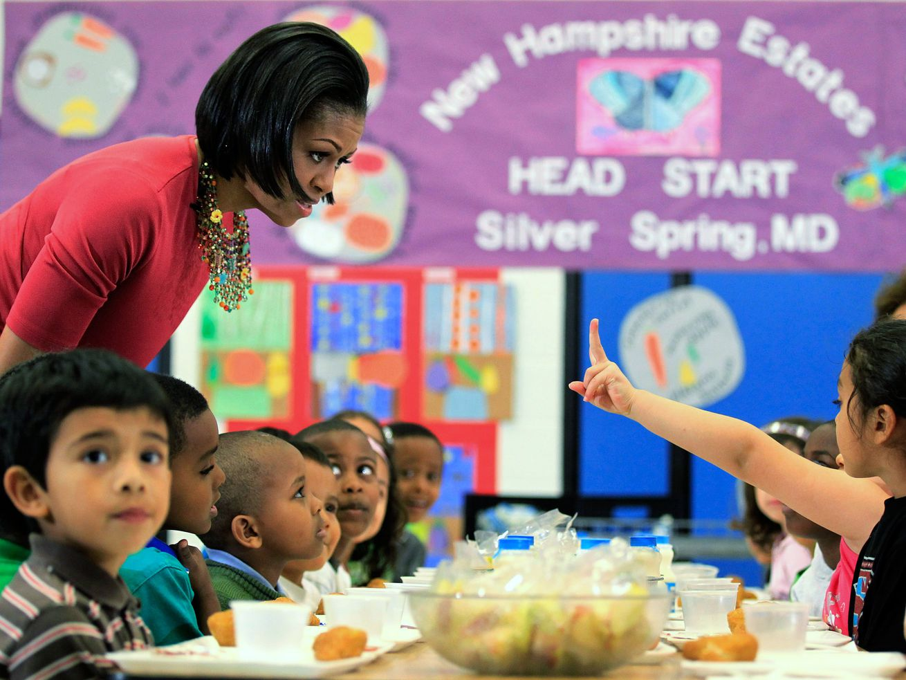 Obama talks with students having lunch.