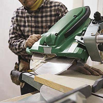 Man Cuts Marked Corner Joints Of Baseboard Trim With Miter Saw