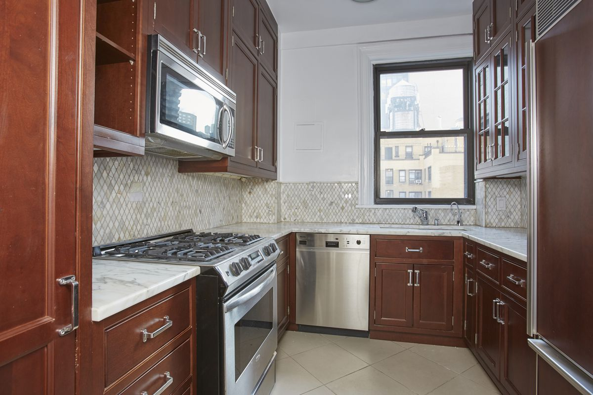 A kitchen with wooden cabinetry and a small window.