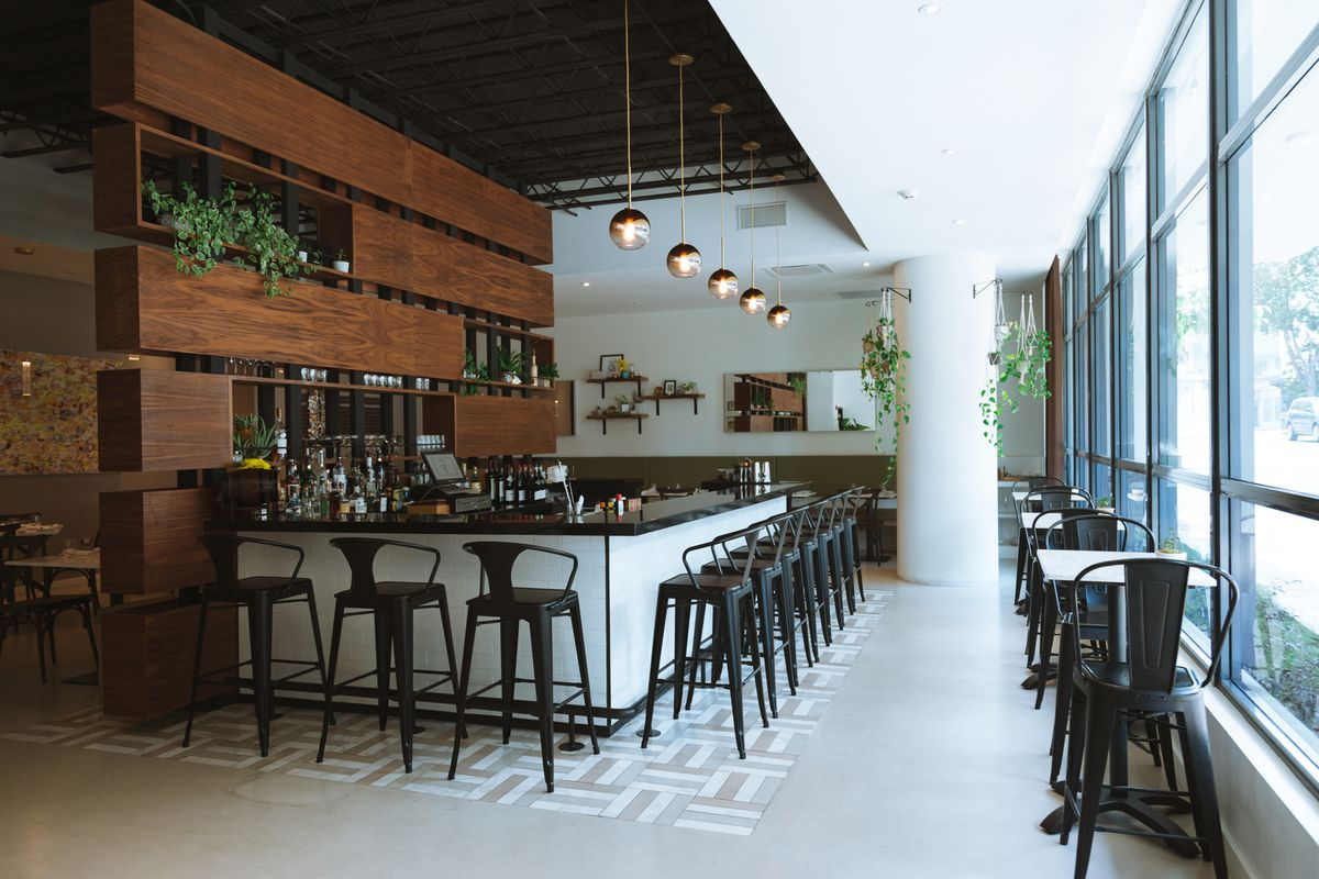 A stylish dining room interior with lots of light, cement flooring, pendant lights over the bar, and a wooden back bar