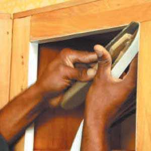 <p>Veneering the inside edges of rails and stiles is a sign of a quality installation. Here the installer applies a rigid thermofoil that matches the new cabinet doors.</p>