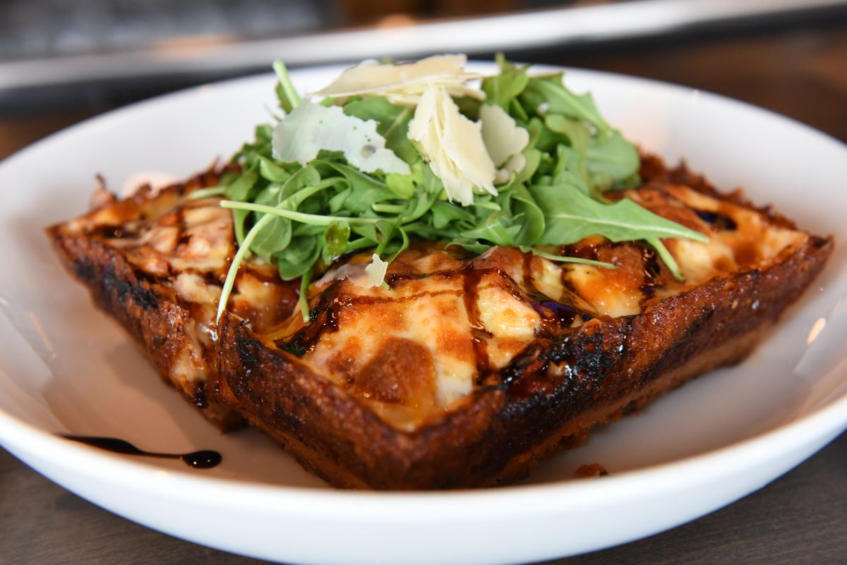 One slice of thick-crust, Detroit-style pizza sits in a shallow white bowl. It's garnished with a drizzle of balsamic glaze and arugula.