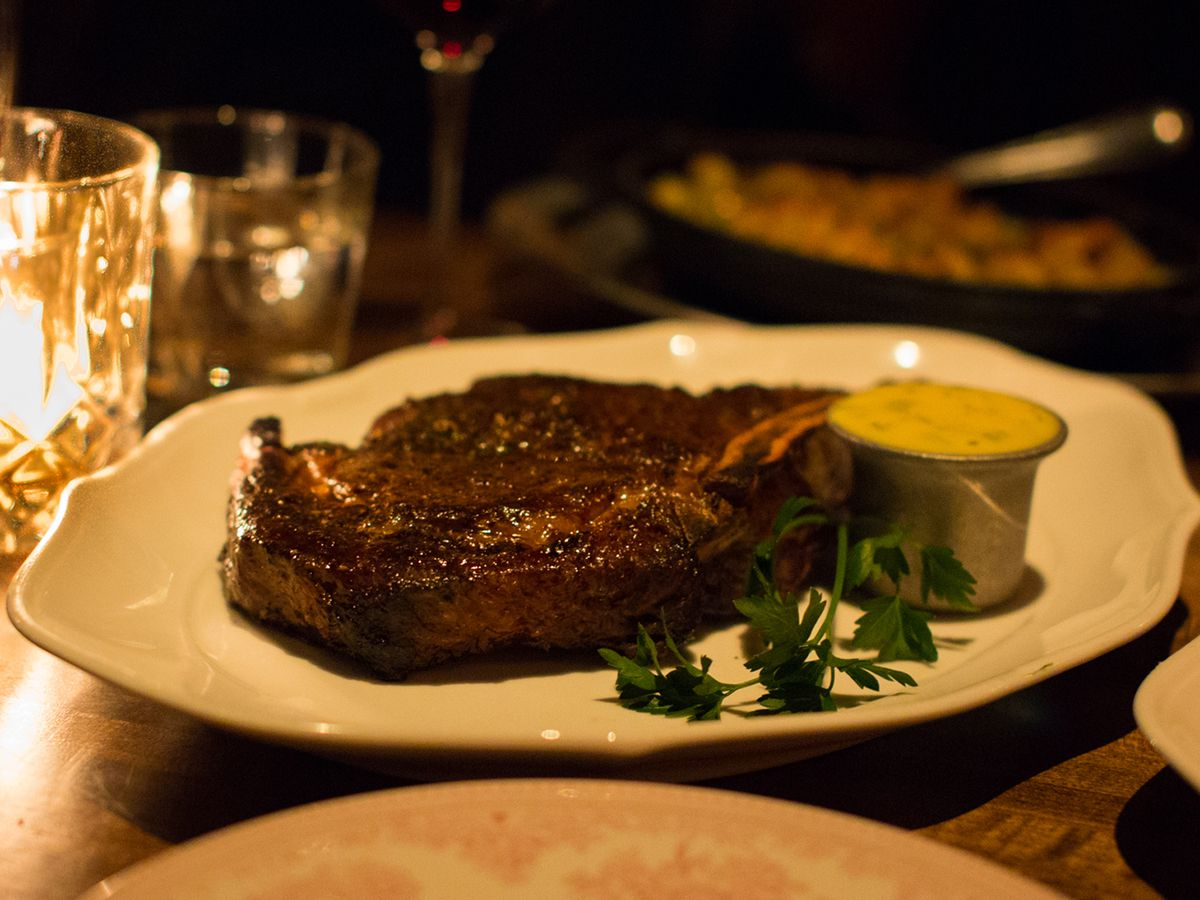 A bone-in rib eye with a cup of Béarnaise on the side.