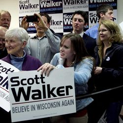 Supporters of Wisconsin Republican Gov. Scott Walker display placards during a visit by Republican presidential candidate, former Massachusetts Gov. Mitt Romney, not shown, during a campaign stop in Fitchburg, Wis., Saturday, March 31, 2012.  The phone bank is used in support of Walker who is facing a recall election in June 2012.