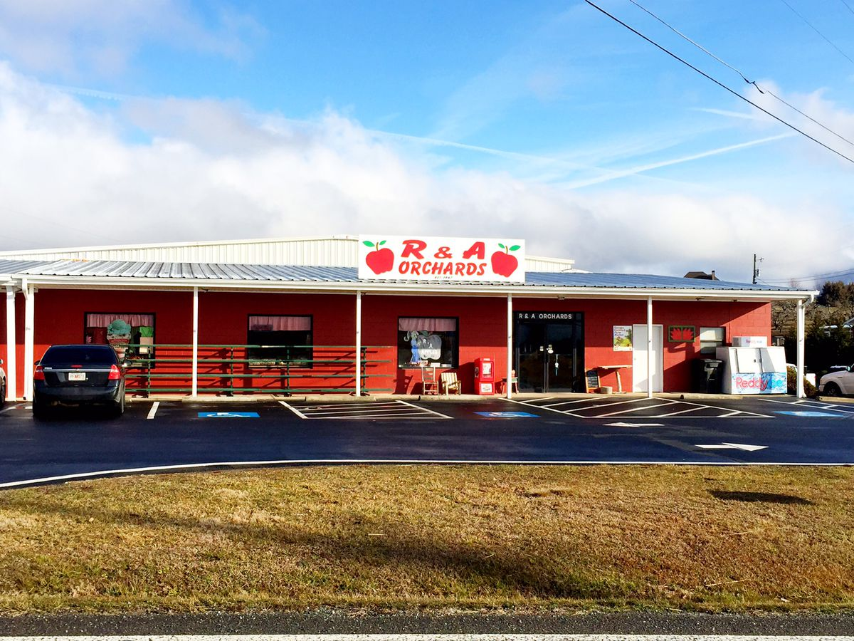 A red building with a white roof. There is a sign on the building which reads: R and A Orchards.
