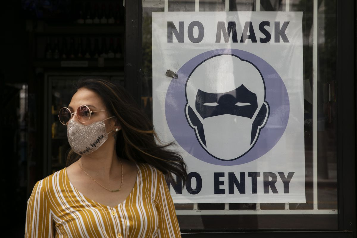 In this June 23, 2020, file photo, a woman walks out of a liquor store past a sign requesting its customers to wear a mask in Santa Monica, Calif. The number of daily U.S. deaths from the coronavirus is declining again after peaking in early August, but scientists are warning that a new bout with the disease this fall could claim more lives.