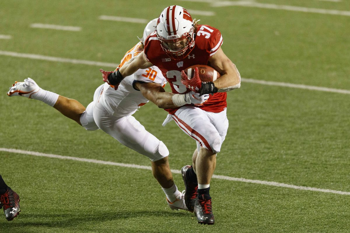 Wisconsin Badgers running back Garrett Groshek rushes with the football against Illinois Fighting Illini defensive back Sydney Brown during the fourth quarter at Camp Randall Stadium.