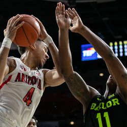 Arizona's Chase Jeter (4) tightly grips an offensive rebound past Baylor's Mark Vital (11) during the Arizona-Baylor game in McKale Center on December 15 in Tucson, Ariz.