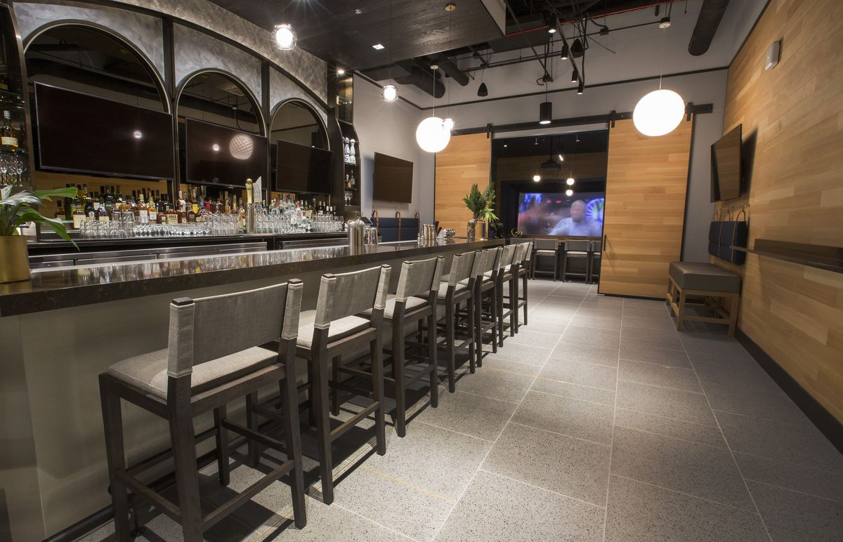 A fully stocked bar with stools leading to a TV screen.