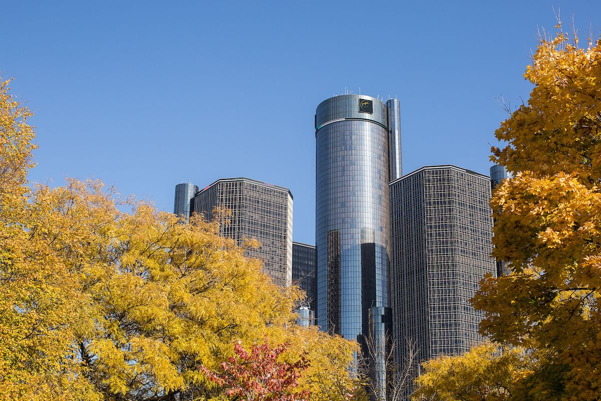 In the foreground are multicolored trees. There is a city skyline with tall buildings in the distance.
