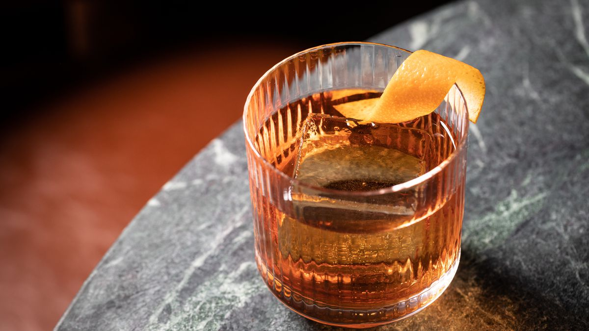 A brown Negroni cocktail in a glass with a large ice cube and a lemon twist