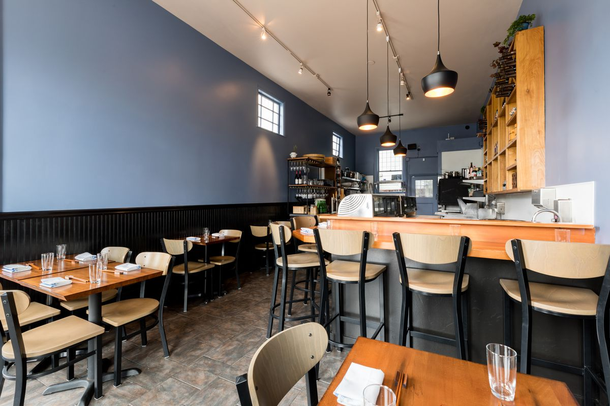 Inside Chisai Sushi Club's 12-seat dining room with blue walls and black beadboard wainscoting.