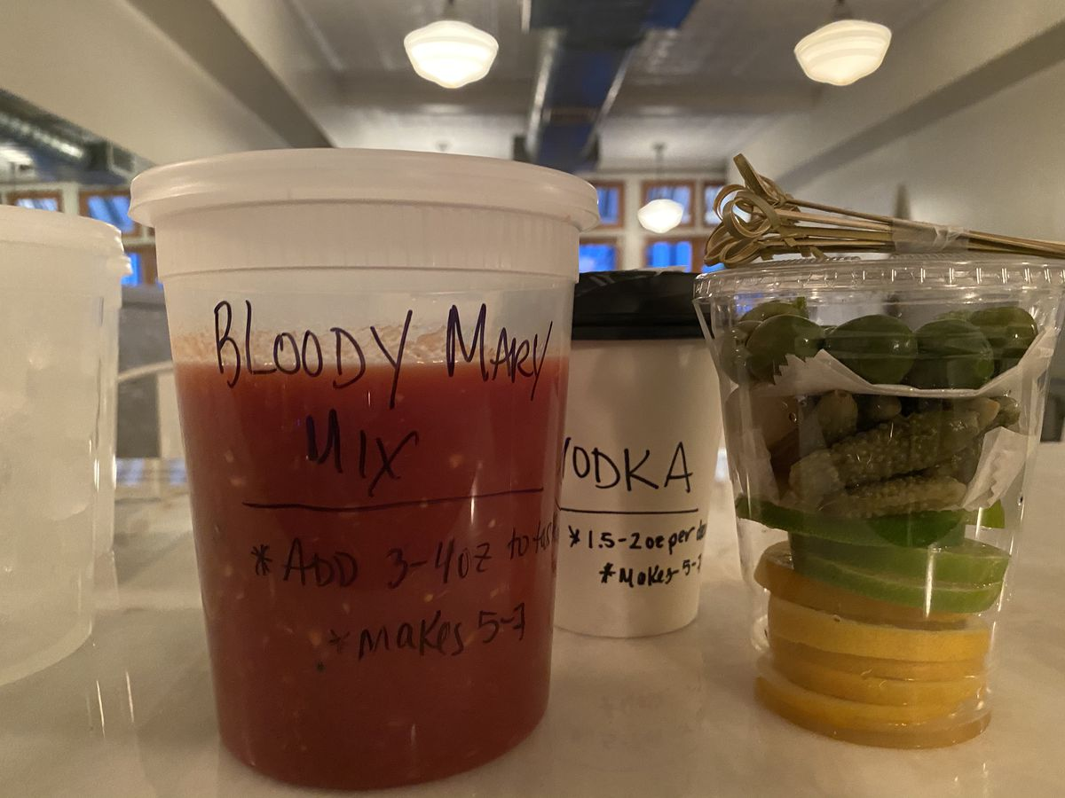 """A to-go container labeled """"Bloody Mary Mix"""" is filled with red liquir, next to a container labeled """"Vodka"""" and container with pickles and other garnishes"""