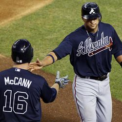 Atlanta Braves' Martin Prada, right, is greeted by teammate Brian McCann (16) after Prada scored on an RBI double hit by Freddie Freeman against the Arizona Diamondbacks during the third inning of a baseball game, Friday, April 20, 2012, in Phoenix.