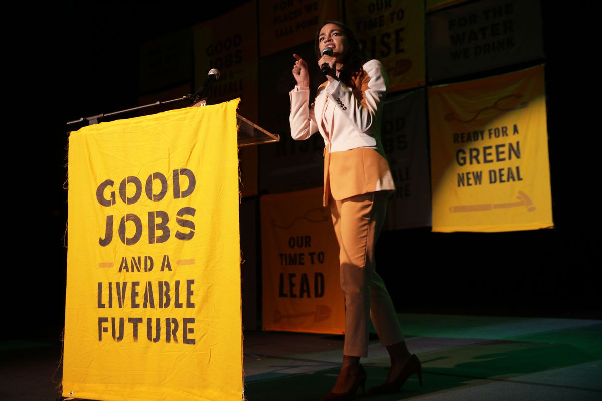 """Alexandria Ocasio-Cortez on stage next to a poster that reads: """"Good jobs and a livable future."""""""