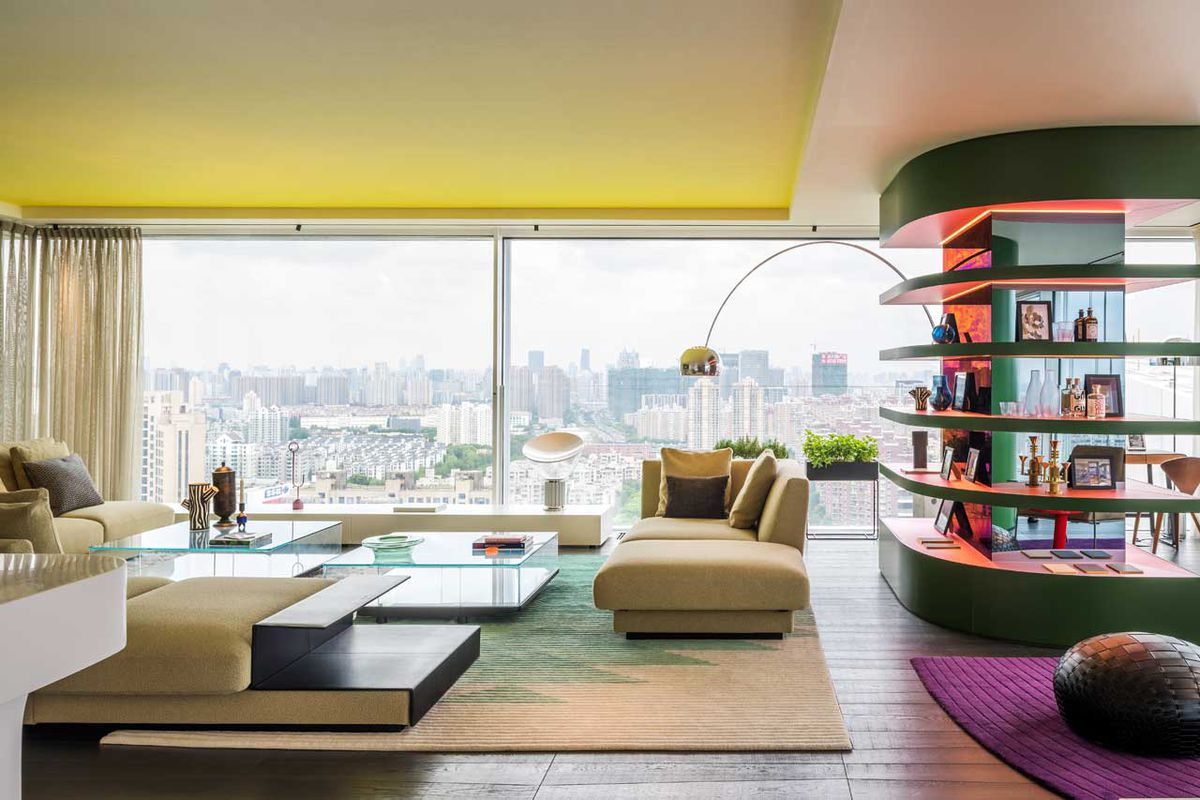 View of living room with full-height glazing framing city views with lounge and curving shelving unit dividing space.