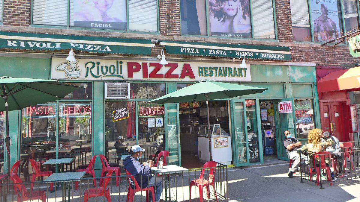 A pizzeria with old fashioned lettering and a seating area out front with red furniture.