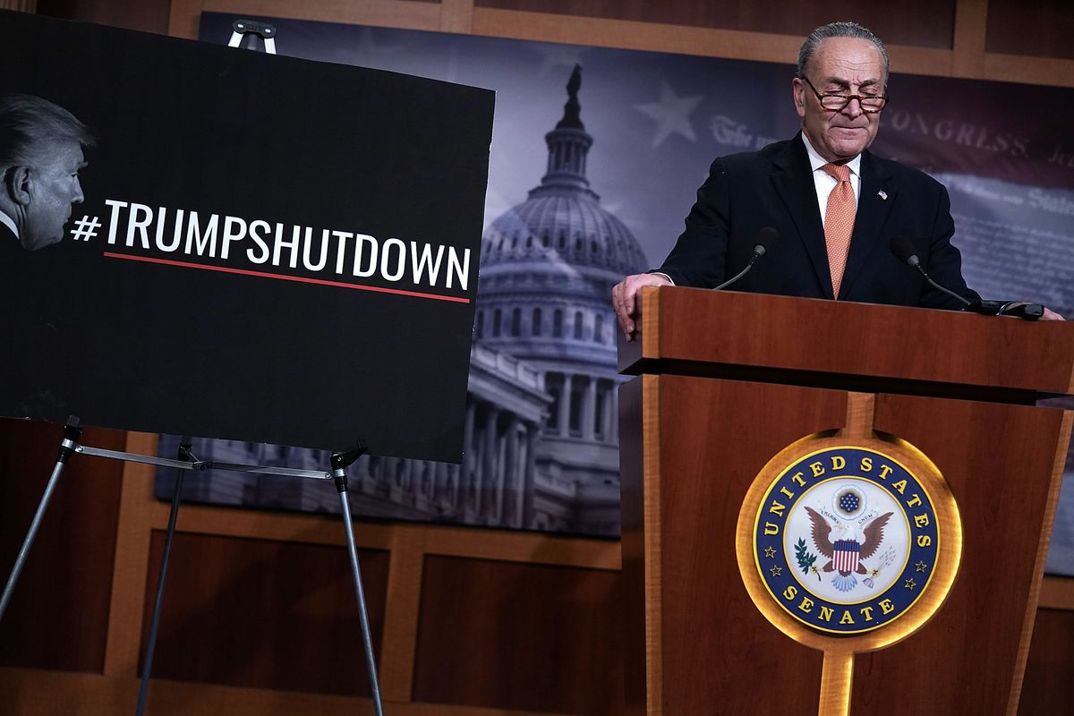 Senate Minority Leader (D-NY) Chuck Schumer next to a sign that reads #TrumpShutdown.