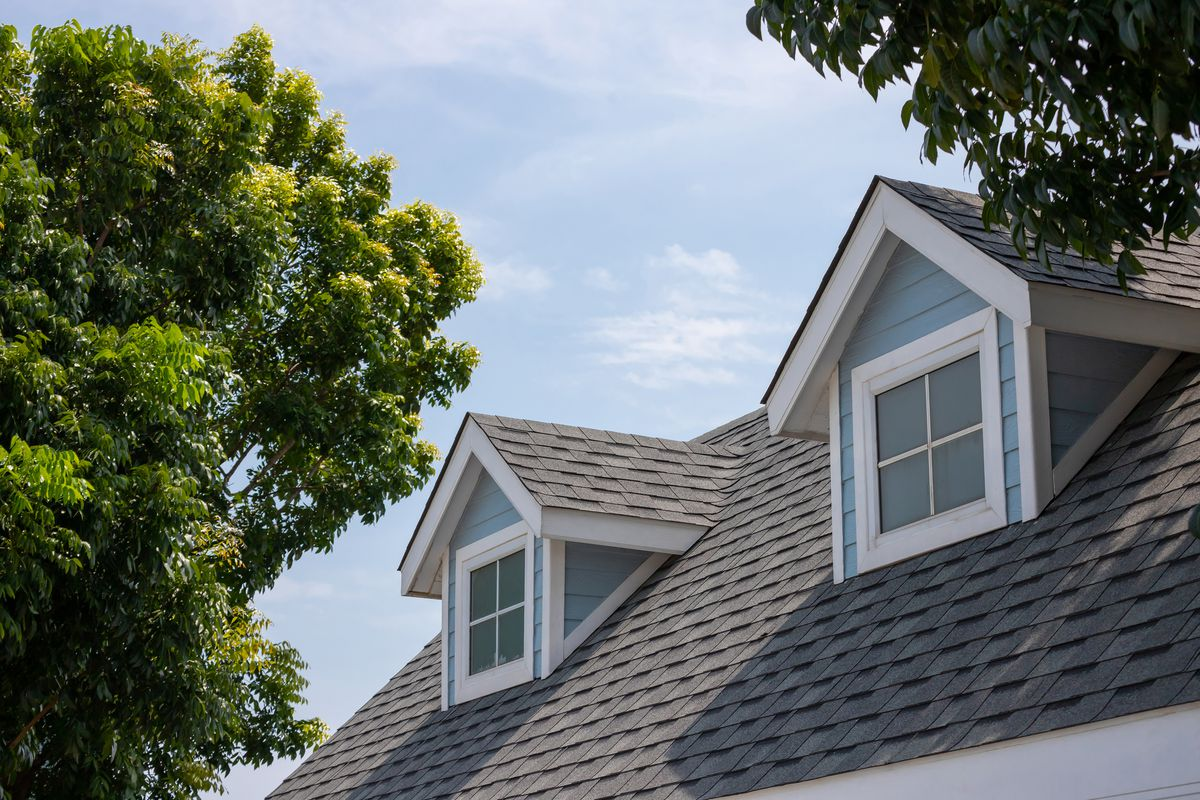 Roof shingles with garret house on top of the house among a lot of trees. dark asphalt tiles on the roof background.