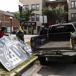 Thomas Taylor (grey shirt), 54, of North Lawndale, and 59-year-old Wayne Flax, of Austin, both workers with McKay Landscaping, work to dismantle and take into storage an old Chicago Housing Authority sign sitting outside the sole remaining building from the Jane Addams Homes in the 1300 block of West Taylor Street, Wednesday, Aug. 21, 2019. The sign once hung at the Robert Taylor Homes, but there are no immediate plans for its restoration or display after years of neglect.