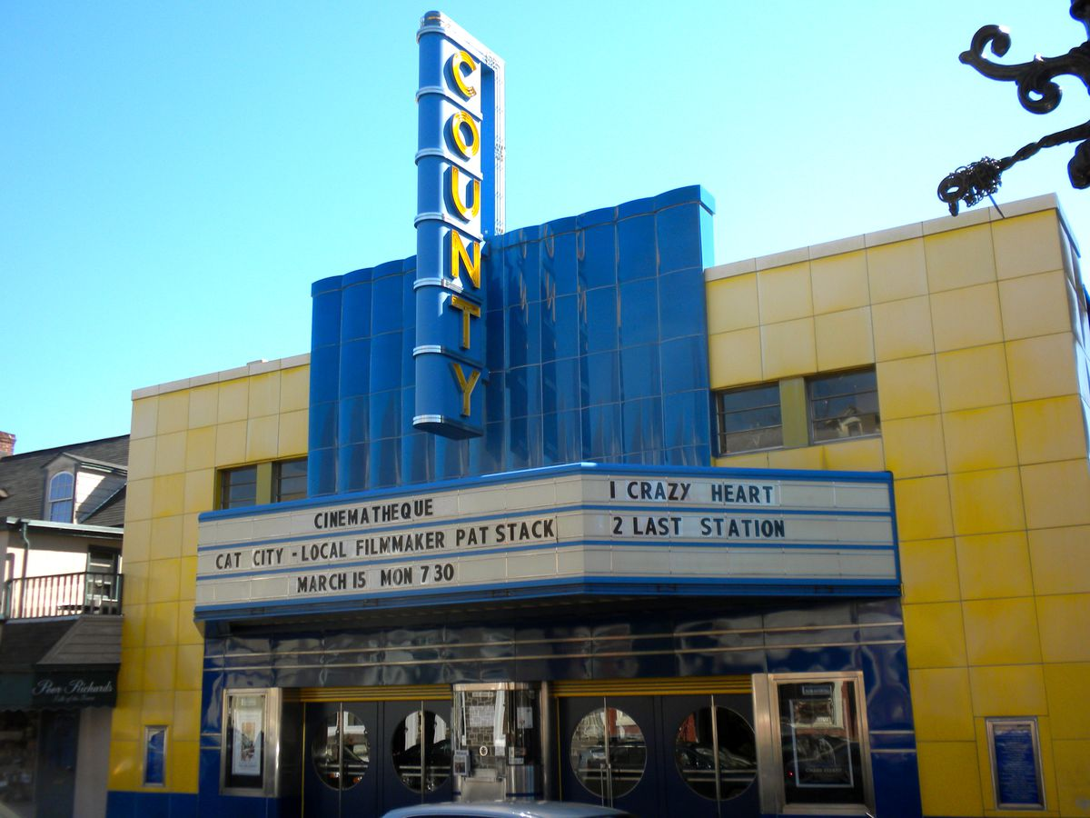 A movie theater in Doylestown, Pennsylvania. There is a sign over the marquee that reads: County. The theater is yellow and the marquee and sign are blue.