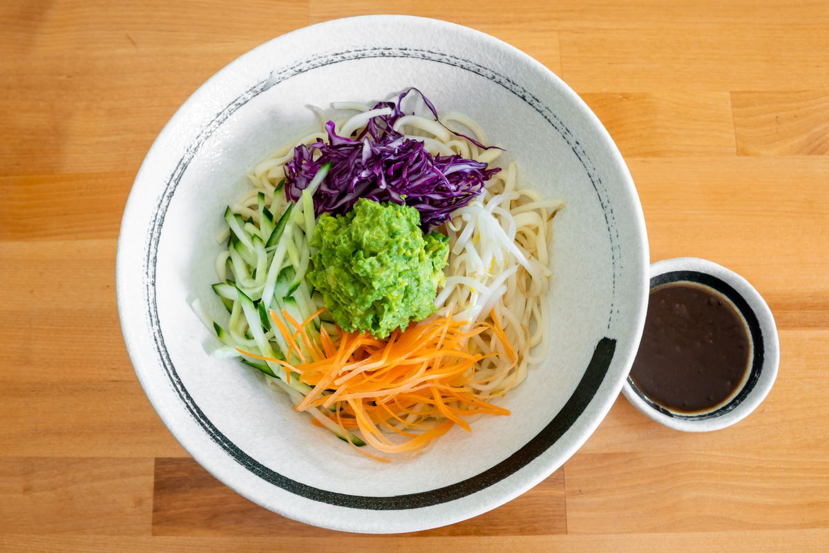 A bowl of noodles topped with shredded carrots, purple cabbage, and cucumber, as well as a big dollop of guacamole in the center