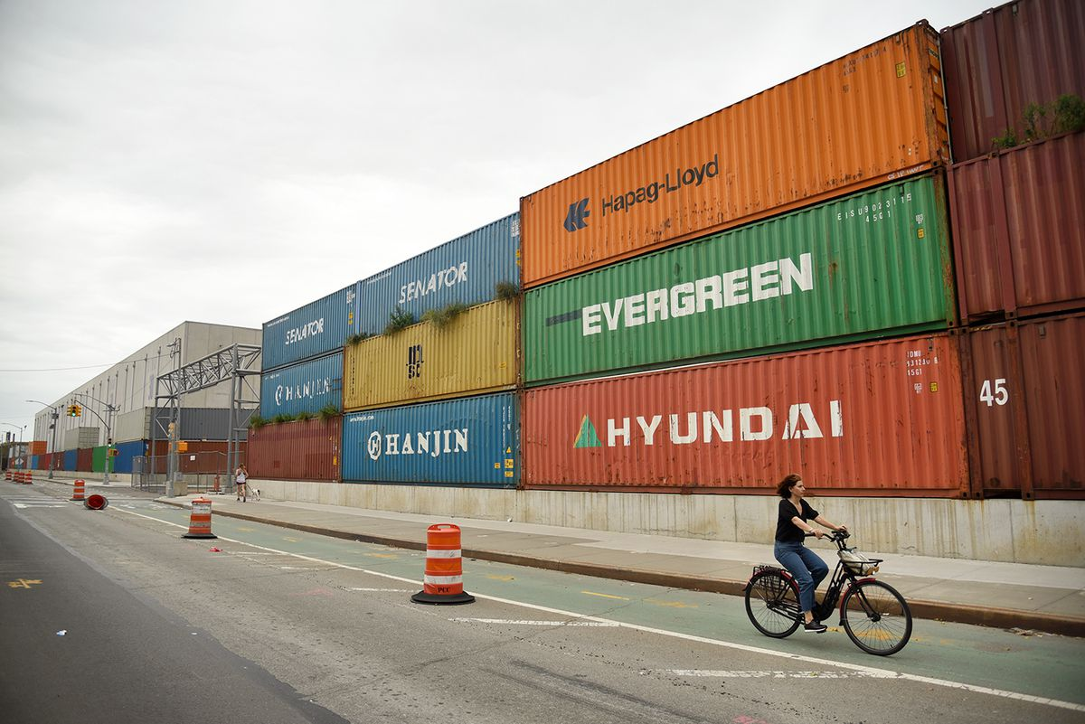 A row of shipping containers next to a street with a bike lane. A woman on a bicycle is in the lane.