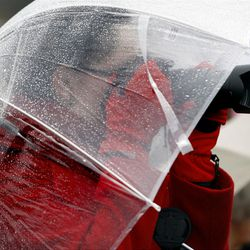 A member of the crowd takes a picture from underneath her umbrella as thousands turn out in the rain Saturday, Oct. 8, 2011 for the ground breaking for the Payson Temple.