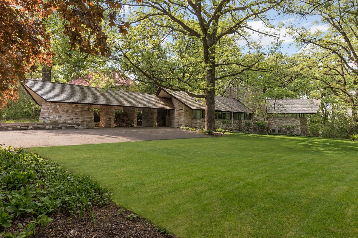 A wide lawn sits in front of a one-story stone house. There are trees around the building.