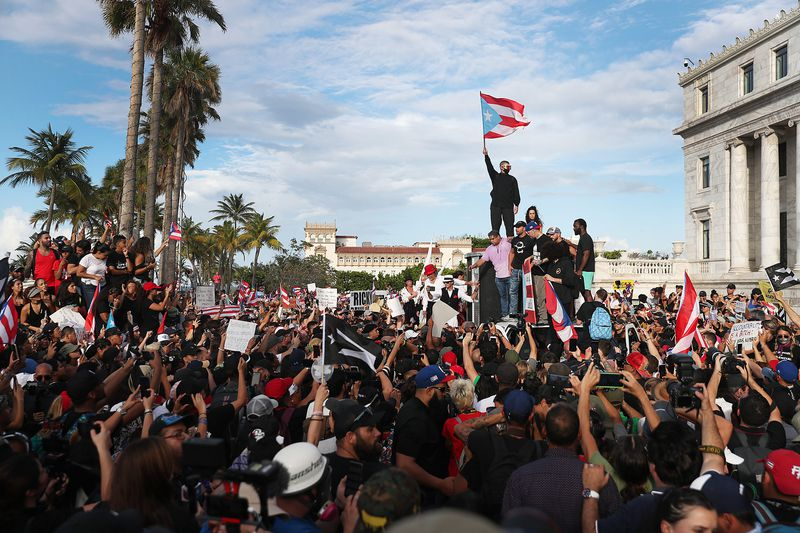 Bad Bunny raises the Puerto Rican flag as Ricky Martin and Puerto Rican rapper Residente address a crowd from atop a vehicle.