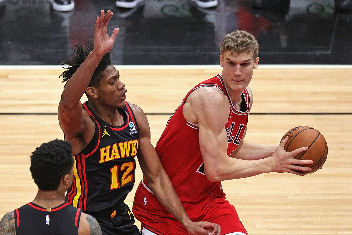 Lauri Markkanen of the Chicago Bulls moves against DeAndre Hunter and John Collins of the Atlanta Hawks at the United Center on December 23, 2020 in Chicago, Illinois.