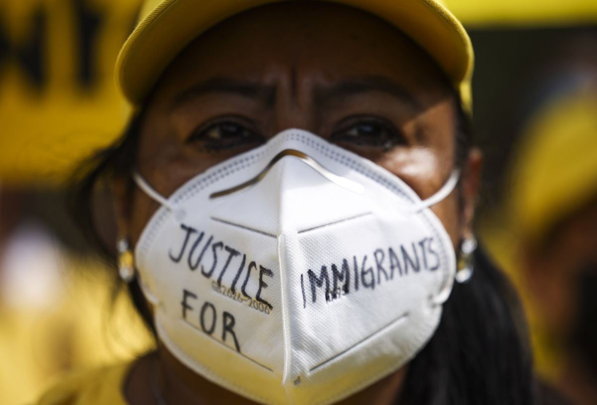 """A person wearing a disposable face mask with the words """"justice for immigrants"""" written it."""