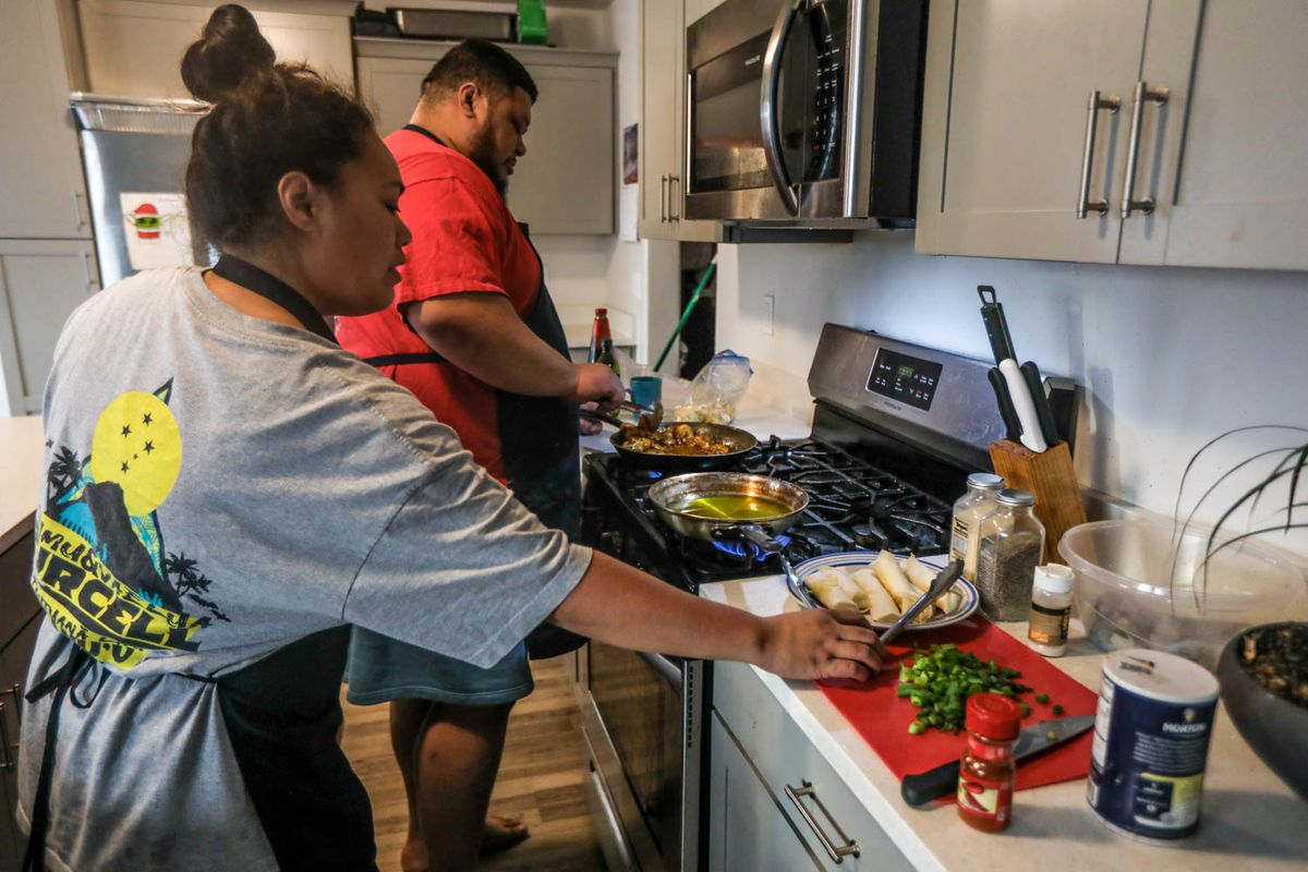 Lola Savaiinaea, left, and Nathan Savaiinaea, right, owners of Sawrap, a microenterprise home kitchen, prepare food to sell in Provo on Thursday, Feb. 18, 2021.
