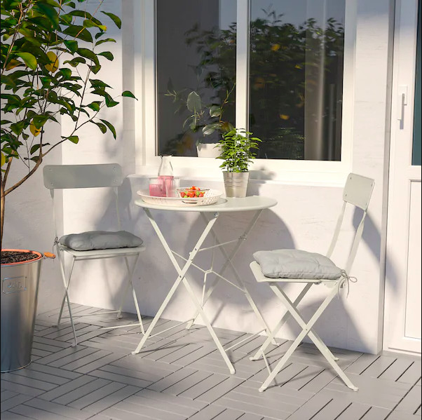 2 white folding chairs and table on patio