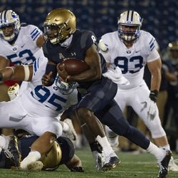 Navy quarterback Dalen Morris, center, runs as BYU defensive lineman Khyiris Tonga (95) defends during the first half of an NCAA college football game, Monday, Sept. 7, 2020, in Annapolis, Md.
