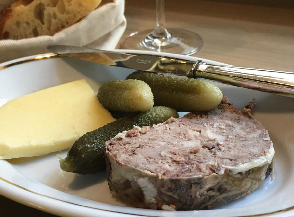 A plate with a slab of pate in front of a few small pickles and a slice of cheese. A knife rests on the plate and a loosely covered bread basket is visible in the background.