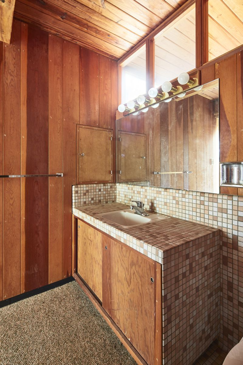 A bathroom with warm wood walls and cabinets, and small tiles.