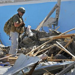 An unidentified armed member of foreign security personnel examines the scene of a car bomb attack in Mogadishu, Somalia Tuesday, June 20, 2017. A number of people are dead after a suicide car bomber in a vehicle posing as a milk delivery van detonated at a district headquarters in Somalia's capital, police said Tuesday.