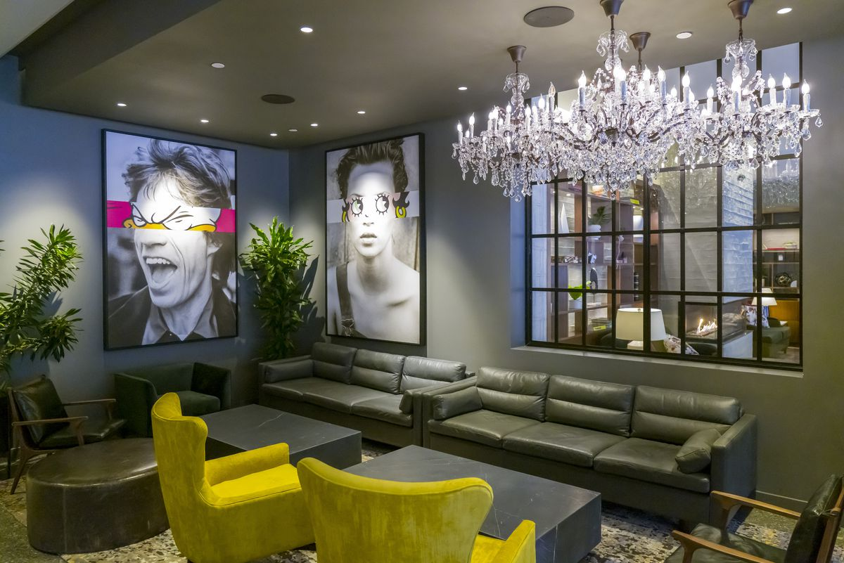 A lounge area of a restaurant features black leather couches, lime green velvet chairs, a crystal chandelier, and a few pieces of pop art