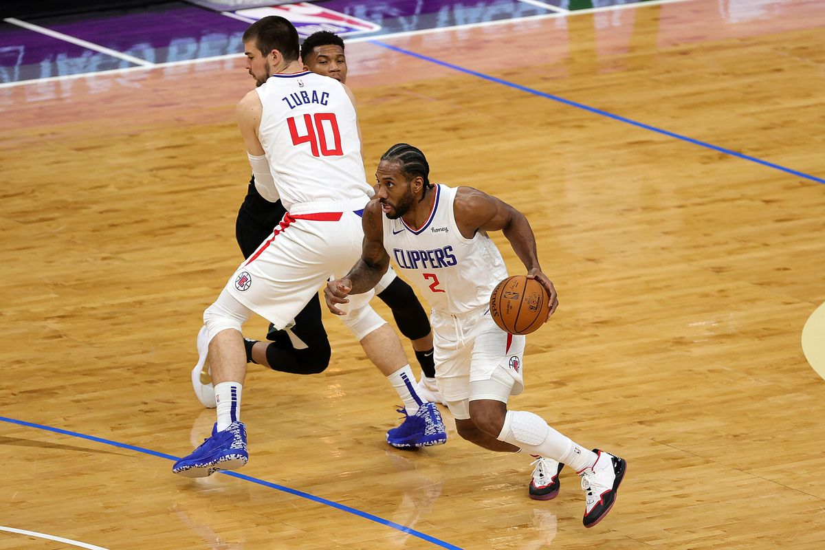 Kawhi Leonard of the LA Clippers drives around a pick set by Ivica Zubac during the first half of a game at Fiserv Forum on February 28, 2021 in Milwaukee, Wisconsin.
