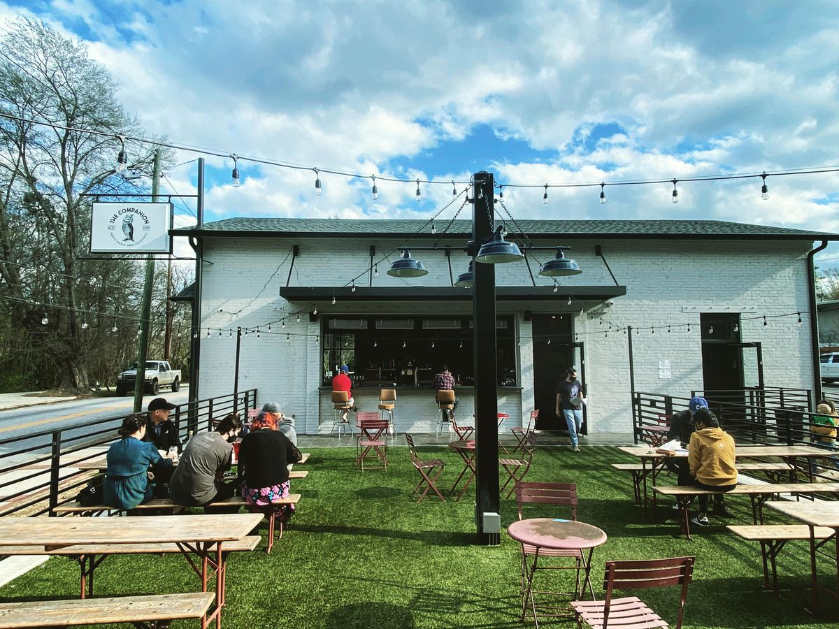 People seating socially distance at picnic tables on the astro turf patio at the Companion in Bolton Atlanta. String lights hang above the patio on sunny day with wispy clouds. Two people sit on bars stools at the outdoor bar